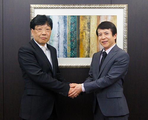 握手を交わすマルベニ質店の勝田守文社長(左)とグローバルトレードの牟田成会長