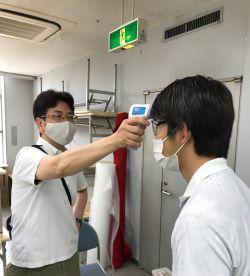 コロナ対策として入場者への検温を行う、共同会主の北山アート・藤生洋社長。37度以上は入場できない。