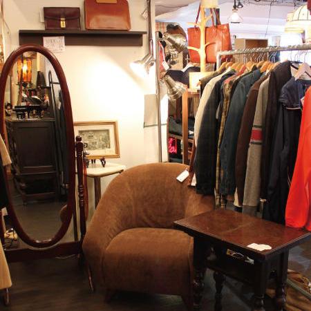 ソファやテーブルなどと洋服を組み合わせて陳列。ソファ周りは座り心地を試してもらえるようにゆったりとしたスペースを確保。販売しているポスターも雰囲気づくりに一役かっている
