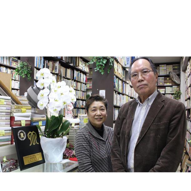 西田書店代表取締役の佐藤健二さん(右)と妻の佐藤純子さん。左にあるのが表彰の盾